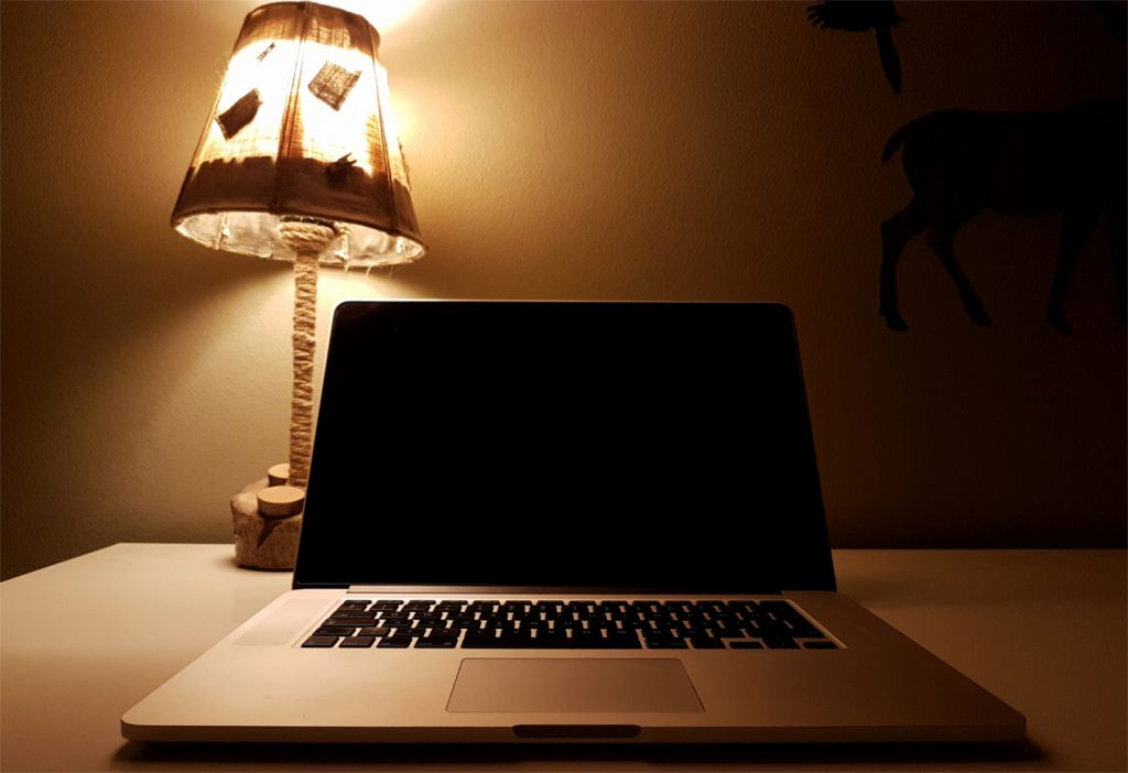 Laptop computer on table with lamp at home