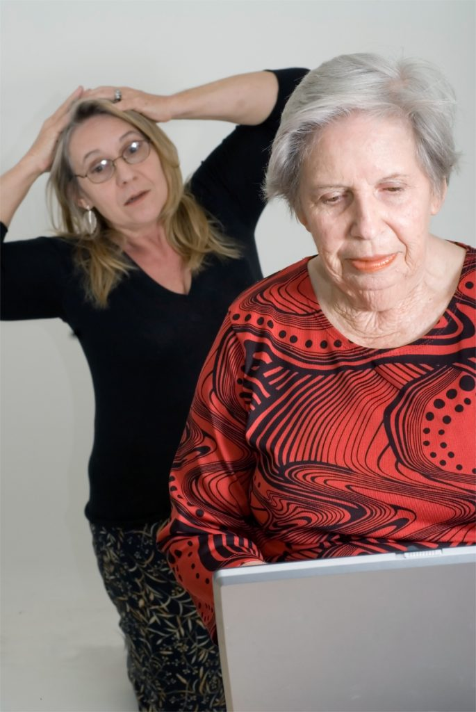 Woman looking over her elderly mother's shoulder while the older lady is working on a laptop