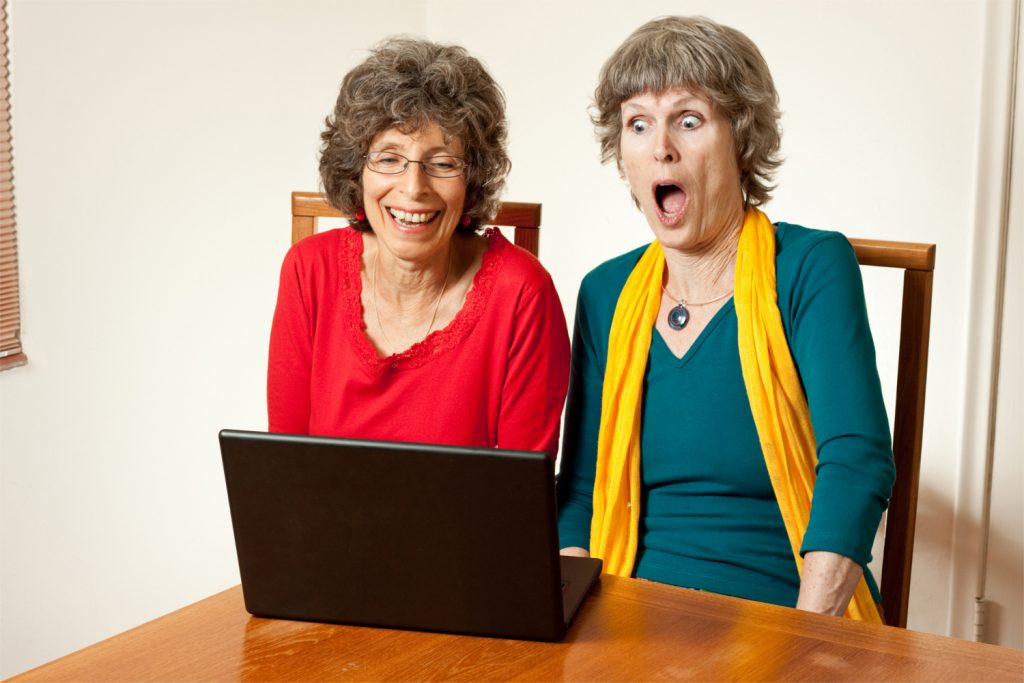Two older ladies with laptop - one has shocked the other