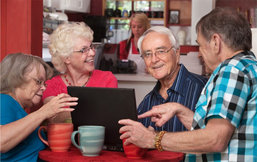 Group of four senior citizens on laptop in cafe